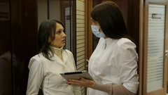 Doctor and a nurse in the clinic hallway discussing patient diagnosis Stock Footage