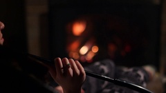 Beautiful woman Smoking a hookah sitting by the fireplace Stock Footage