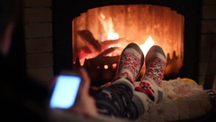 Girl resting by the fireplace and communicate on your smartphone Stock Footage