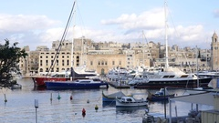 Birgu, Malta buildings architecture and yachts moored to the marina quay morning Stock Footage