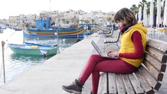 Woman freelancer work type laptop computer sit at seafront bench of Malta Stock Footage