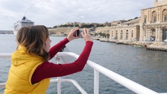 Valletta, Malta - woman tourist take picture of city line from moving ferryboat Stock Footage