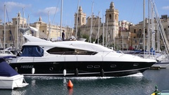 Birgu, Malta - big yacht goes along harbor and picturesque city buildings view Stock Footage