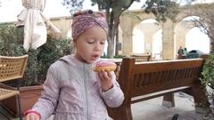 Valletta, Malta - Child girl eat chew sweet pastry donut Stock Footage