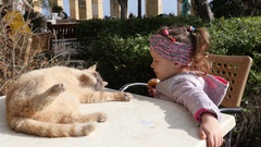 Valletta, Malta - Child girl eat pastry and play with cat lying on street table Stock Footage