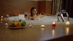 Woman drinking red wine in bath with foam Stock Footage