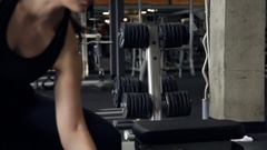 The sportswoman raises and lowers the left hand dumbbell in the gym Stock Footage