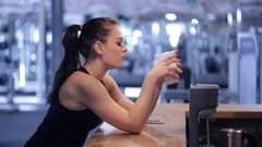 Young woman drinking a protein shake and looking at the phone Stock Footage