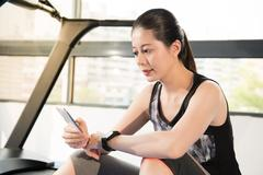 Asian woman rest on treadmill use smartphone and smartwatch Stock Photos