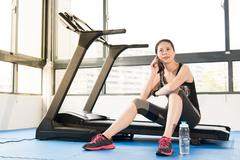 Asian woman rest sitting treadmill use smartphone and smartwatch Stock Photos