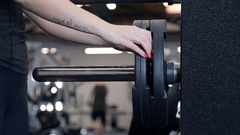 Athlete removes iron wheels with barbells for bench press in gym Stock Footage