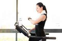 Asian woman running treadmill use smartwatch check pulse rate Stock Photos