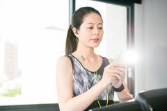 Sport asian woman running treadmill use smartphone listening music Stock Photos