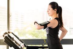 Beautiful asian woman running treadmill use smartwatch listening music Stock Photos