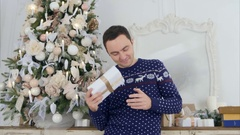 Surprised young man shaking his Christmas present trying to guess what's inside Stock Footage