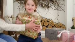 Cute little boy checking wrapped Christmas present and happily dancing with it Stock Footage