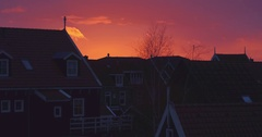 Drone crane shot of sunset in marken filming old fishing houses and harbor Stock Footage