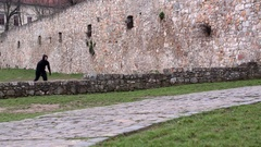 Young athlete in a black suit making a somersault on the stones of a castle Stock Footage