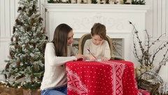 Young mother helping her little son to write a letter to Santa Claus Stock Footage