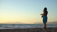 Photographer woman taking pictures at a beach with a sunset Stock Footage