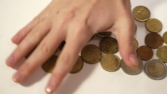 Female hand rakes up coins and change them at 100 dollars Stock Footage