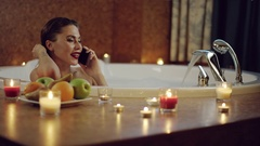 Woman with cosmetics in bath with foam talking on phone Stock Footage