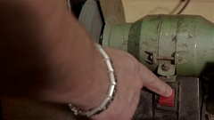Worker uses grindstone to repair drill in old workshop. Close up view Stock Footage