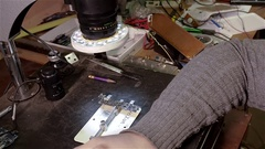 Engineer checking quality of repair of motherboard of smartphone iphone using Stock Footage