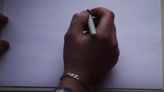 The hand of the man draws a smiley face on a white sheet of paper Stock Footage