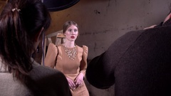 Girl model poses in a dress in a dirty basement photo session Stock Footage