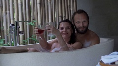 Happy couple raising toast to camera and drinking wine in bathtub Stock Footage