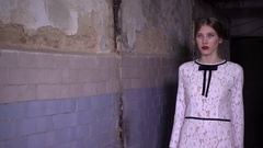 Girl model catwalk in a dress in a dirty basement photo session Stock Footage