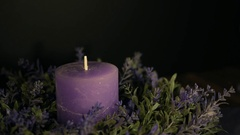 A woman lights a cdecorative candle on a black background Stock Footage