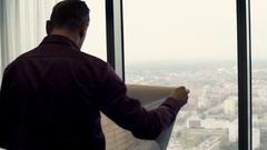Architect reading blueprints looking at the city by window at office Stock Footage