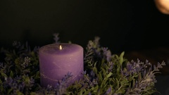 Woman's hand lights a violet candle with a lighter Stock Footage
