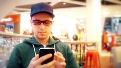 Programmer wearing black rim glasses taps on his mobile phone touchscreen in a Stock Footage