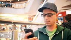 Young caucasian man wearing cap and black rim glasses taps on his mobile phone Stock Footage