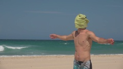 Man with Sea towel Covering Face, Arms Open, Beach Stock Footage