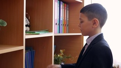 A schoolboy taking an exercise book from a bookshelf. Mid shot. Stock Footage