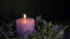 Woman blowing a decorative violet candle. Stock Footage