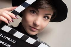 Portrait of young actress holding a movie clapper Stock Photos