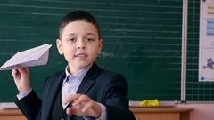 A smiling school boy throwing paper airplane in a classroom. Slow motion. Stock Footage