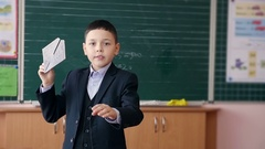 A school boy throwing paper airplane in a classroom. Slow motion. Stock Footage