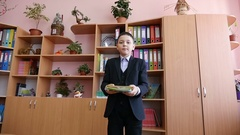 A happy school boy throwing up exercise books in his class. Slow motion. Stock Footage