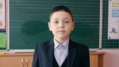 A pupil showing two thumb up gesture in his class.Slow motion. Stock Footage