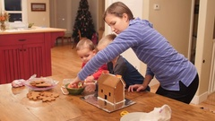 A family decorates a small ginger bread house for christmas Stock Footage