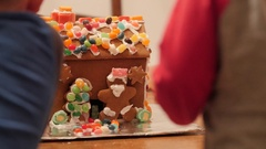 A family decorating adorable ginger bread house for christmas night Stock Footage