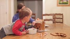 A family decorates adorable ginger bread house for christmas Stock Footage