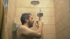 Handsome bearded man taking shower. Slow motion shot, warm colors Stock Footage