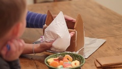 Family decorates a small ginger bread house Stock Footage